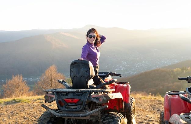 Jonge gelukkige vrouwelijke bestuurder genieten van extreme rit op atv quad motor in herfst bergen bij zonsondergang.