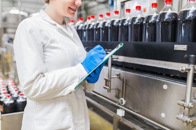 Jonge gelukkige vrouwelijke werknemer in bottelarij die sapflessen controleert vóór verzending. inspectie kwaliteitscontrole.