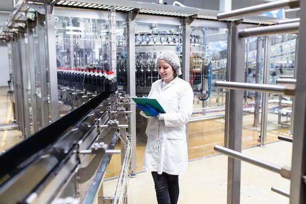 Jonge gelukkige vrouwelijke werknemer in bottelarij die sapflessen controleert vóór verzending