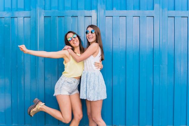 Jonge gelukkige vrouwen knuffelen en plezier maken