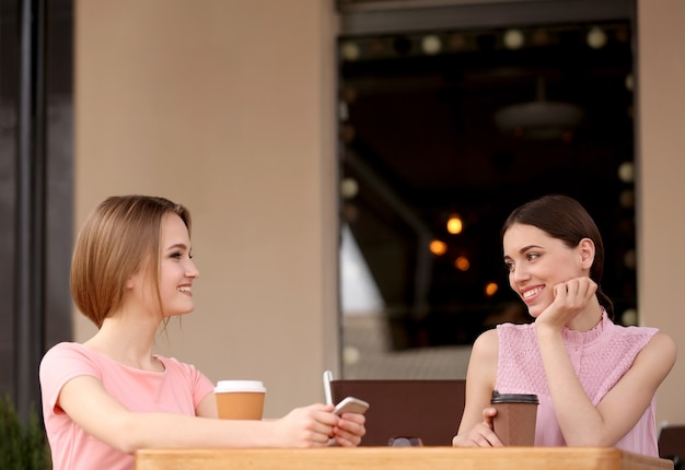 Jonge gelukkige vrouwen koffie drinken en praten in café