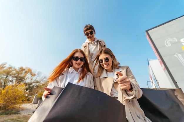 Jonge gelukkige vrouwen met boodschappentassen die op straat lopen.