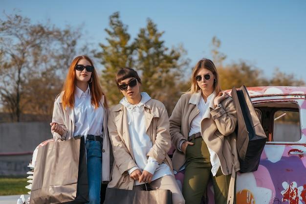 Jonge gelukkige vrouwen met boodschappentassen poseren in de buurt van een oude versierde auto