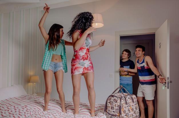 Jonge gelukkige vrouwen paar dansen over een bed en hun vrienden lachen om de kamerdeur te openen. jongeren levensstijl concept.