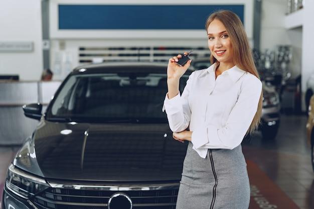 Jonge gelukkige vrouwenkoper / verkoper dichtbij de auto met in hand sleutels