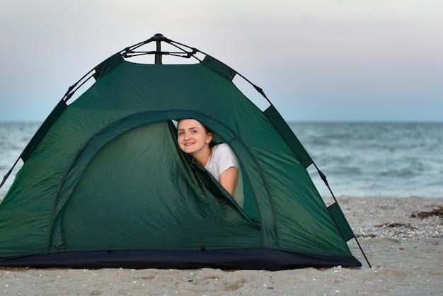 Jonge gelukkige vrouwentoeristen die uit tent gluren. kamperen aan zee.