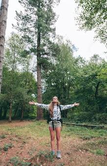 Jonge gelukkige wandelaar vrouw met rugzak die haar armen opheft en geniet van het bos. vrijheid en natuur concept.