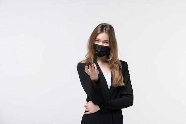 Jonge, gelukkige zakenvrouw in pak met een chirurgisch masker en iemand wijzend op een geïsoleerde witte muur
