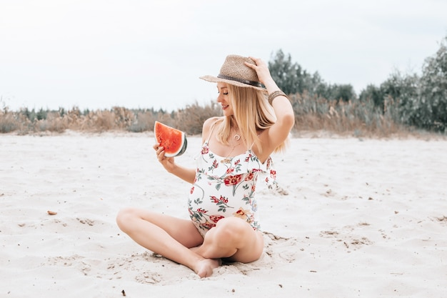 Jonge gelukkige zwangere vrouw in een zwempak en hoed met watermeloen