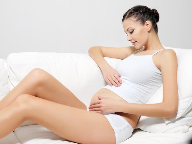 Jonge gelukkige zwangere vrouwenzitting op bank