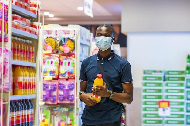 Jonge gelukkige zwarte man die winkelt met een medisch masker