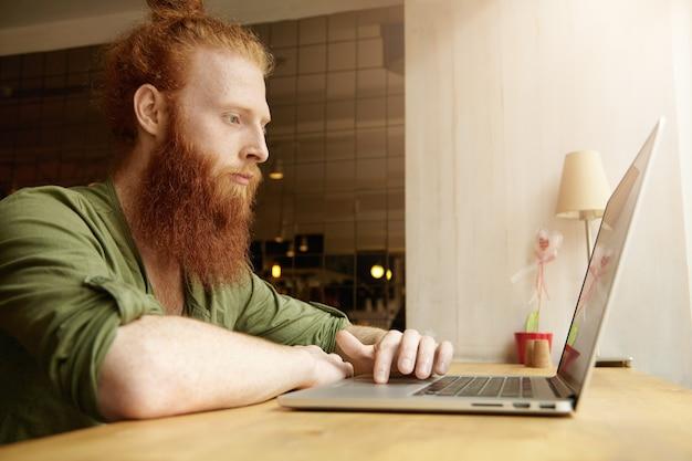 Jonge gember man met behulp van laptop