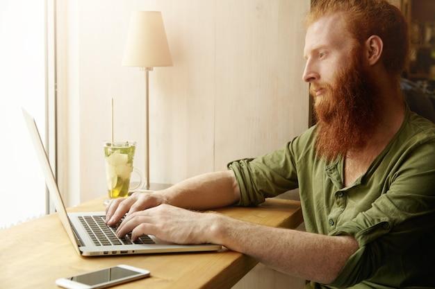 Jonge gember man met laptop in café