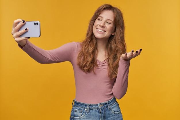 Jonge gemberpositieve vrouw, met sproeten en golvend haar, videochat met haar vriendje, glimlacht en voelt zich gelukkig