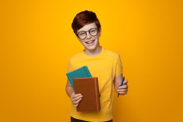 Jonge gemberschooljongen die enkele mappen vasthoudt, glimlacht op een gele studiomuur terwijl hij een bril en een casual t-shirt draagt