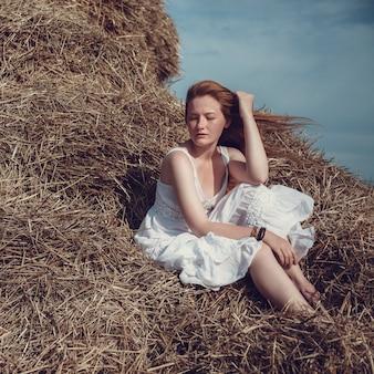 Jonge gembervrouw in het tarweveld die er ontspannen uitziet. vrouw op een agrarisch gebied tijdens zonsondergang.