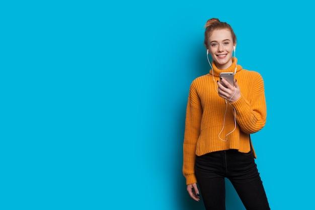 Jonge gembervrouw met sproeten luistert naar muziek op een blauwe muur met vrije ruimte met een koptelefoon