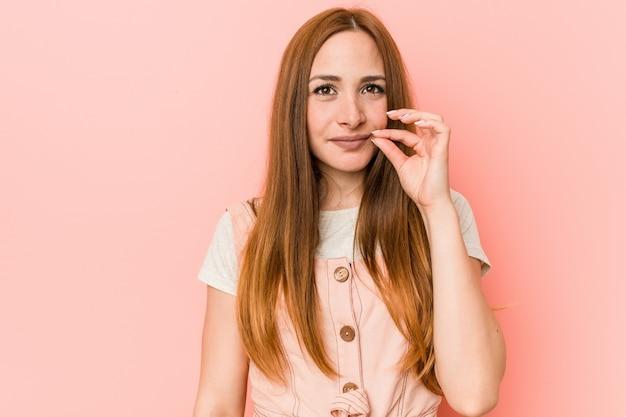 Jonge gembervrouw met sproeten met vingers op lippen die een geheim houden