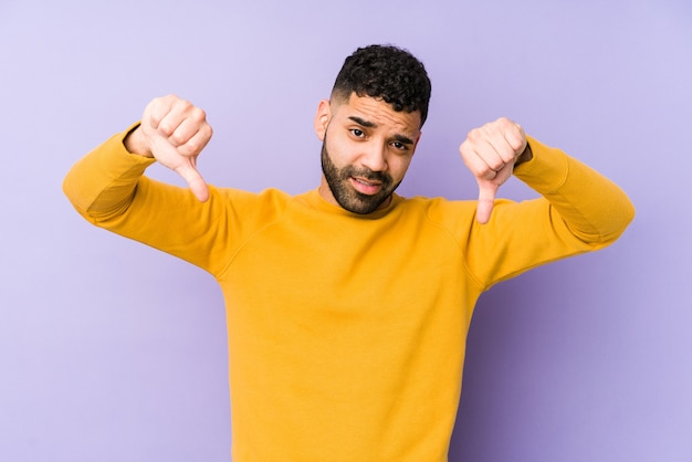 Jonge gemengd ras arabische man geïsoleerd duim omlaag tonen en afkeer uiten.