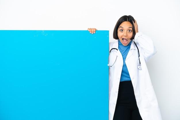 Jonge gemengd ras arts vrouw met een groot bord geïsoleerd verrast en wijzende vinger naar de zijkant