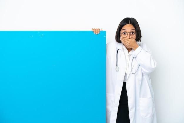Jonge gemengd ras arts vrouw met een groot bordje geïsoleerd op een witte achtergrond die de mond bedekt met handen
