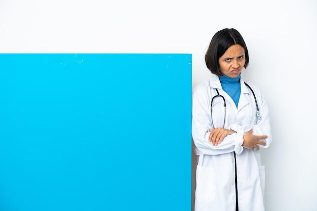 Jonge gemengd ras arts vrouw met een groot bordje geïsoleerd op een witte achtergrond met ongelukkige expression