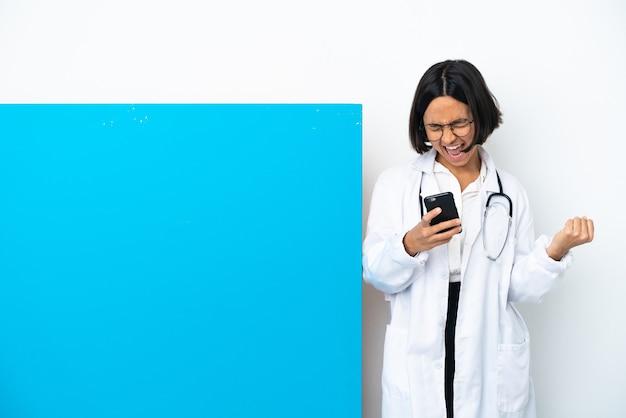Jonge gemengd ras arts vrouw met een groot bordje geïsoleerd op een witte achtergrond met telefoon in overwinning positie