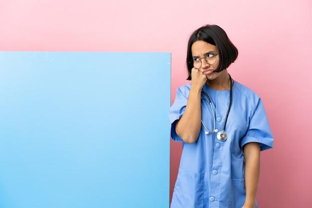 Jonge gemengd ras chirurg vrouw met een grote banner geïsoleerde achtergrond met vermoeide en verveelde expressie