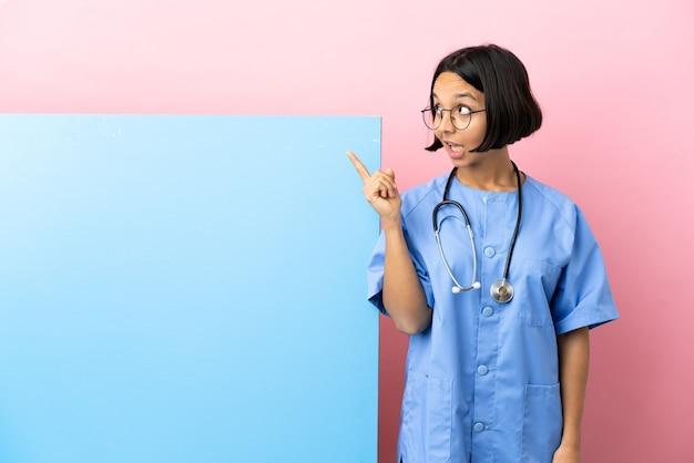 Jonge gemengd ras chirurg vrouw met een grote banner over geïsoleerde achtergrond van plan om de oplossing te realiseren terwijl het opheffen van een vinger