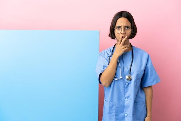 Jonge gemengd ras chirurg vrouw met een grote banner over geïsoleerde achtergrond verrast en geschokt terwijl ze naar rechts kijkt