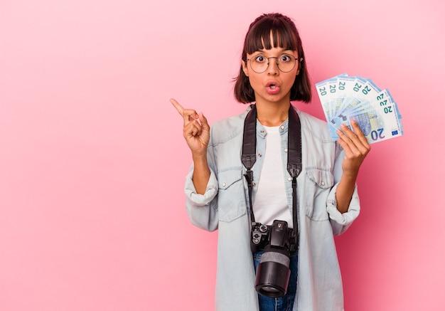 Jonge gemengd ras fotograaf vrouw met rekeningen geïsoleerd op roze achtergrond wijzend naar de zijkant