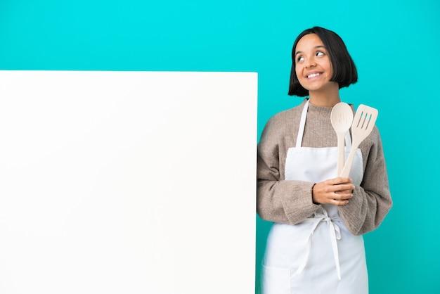 Jonge gemengd ras kok vrouw met een groot bord geïsoleerd op blauwe achtergrond een idee denken tijdens het opzoeken