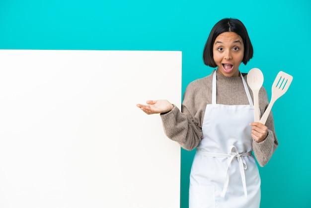 Jonge gemengd ras kok vrouw met een groot bord geïsoleerd op blauwe achtergrond met verrassing en geschokte gezichtsuitdrukking