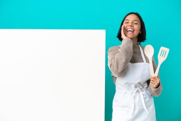 Jonge gemengd ras kok vrouw met een groot bord geïsoleerd op blauwe achtergrond schreeuwen en iets aankondigen