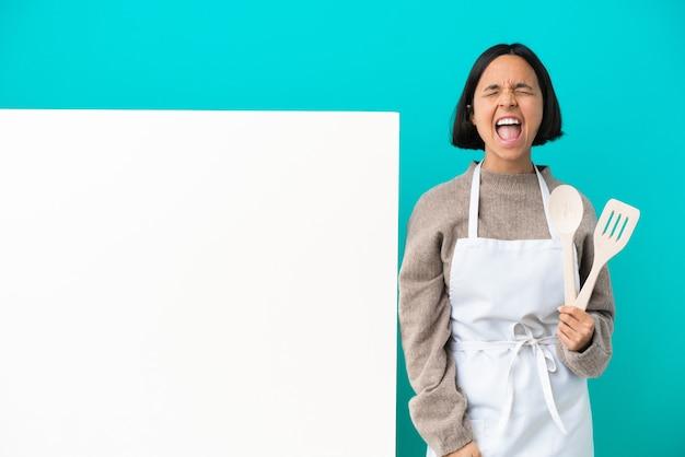 Jonge gemengd ras kok vrouw met een groot bord geïsoleerd op blauwe achtergrond schreeuwen naar voren met wijd open mond
