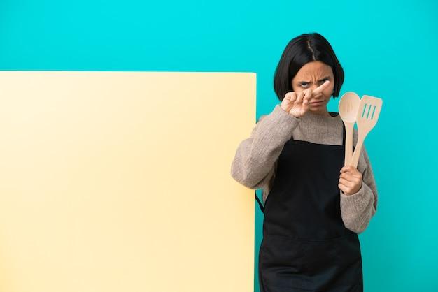 Jonge gemengd ras kok vrouw met een groot bord geïsoleerd op blauwe achtergrond stop gebaar maken met haar hand om een act te stoppen
