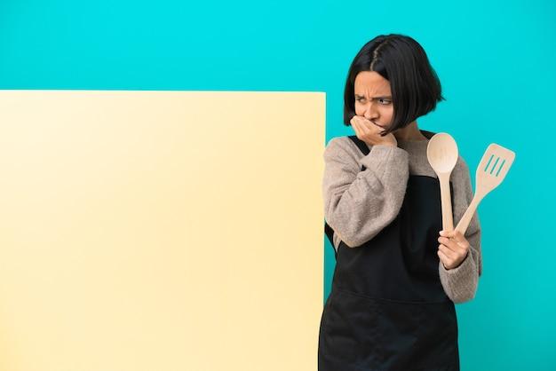 Jonge gemengd ras kok vrouw met een groot bord geïsoleerd op blauwe achtergrond twijfels