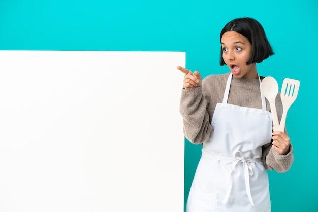 Jonge gemengd ras kok vrouw met een groot bord geïsoleerd op blauwe achtergrond verrast en naar boven gericht