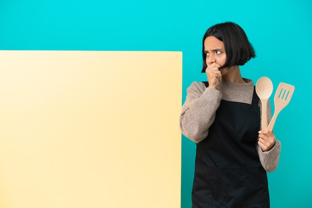 Jonge gemengd ras kok vrouw met een groot bord geïsoleerd op een blauwe achtergrond die de mond bedekt en naar de zijkant kijkt Premium Foto