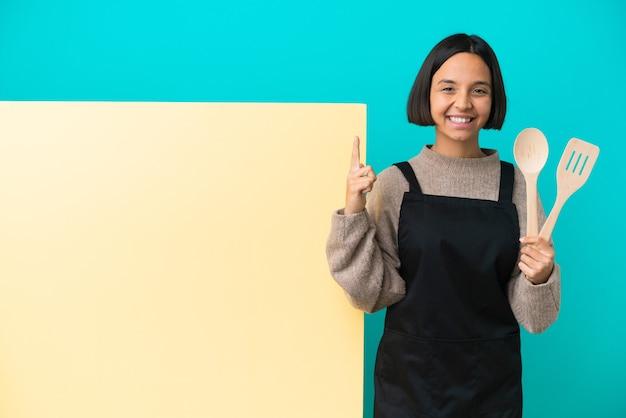 Jonge gemengd ras kok vrouw met een groot bord geïsoleerd op een blauwe achtergrond die een geweldig idee benadrukt
