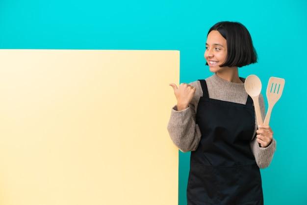 Jonge gemengd ras kok vrouw met een groot bord geïsoleerd op een blauwe achtergrond die naar de zijkant wijst om een product te presenteren