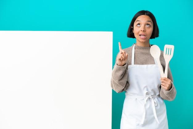 Jonge gemengd ras kok vrouw met een groot bord geïsoleerd op een blauwe achtergrond met een teken van stilte gebaar vinger in de mond steken