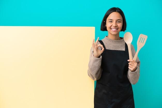 Jonge gemengd ras kok vrouw met een groot bordje geïsoleerd op een blauwe achtergrond met ok teken met twee handen