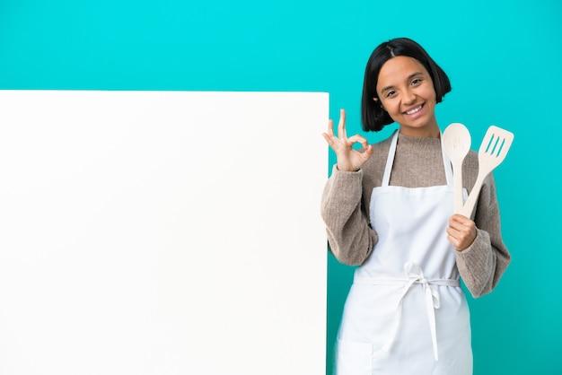 Jonge gemengd ras kok vrouw met een groot bordje geïsoleerd op een blauwe achtergrond met ok teken met vingers