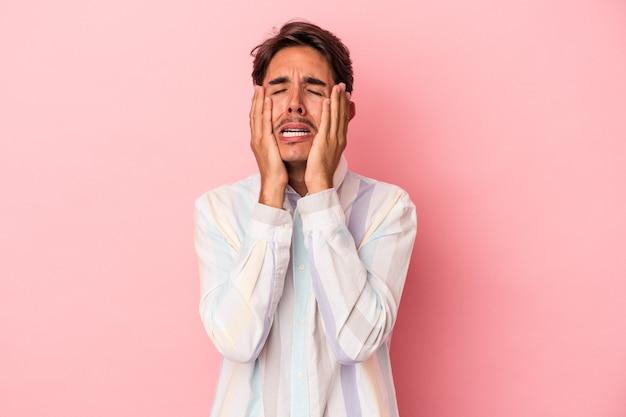 Jonge gemengd ras man geïsoleerd op een witte achtergrond huilen, ongelukkig met iets, pijn en verwarring concept.