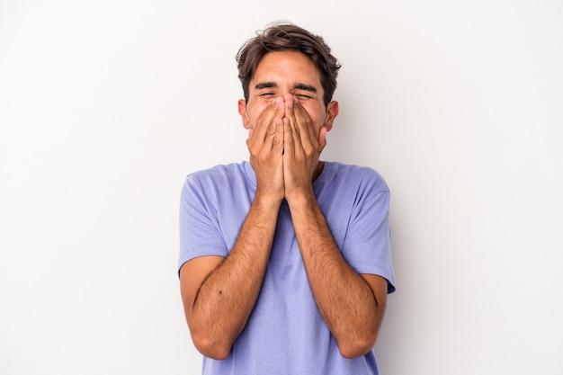 Jonge gemengd ras man geïsoleerd op een witte achtergrond lachen om iets, mond bedekken met handen.