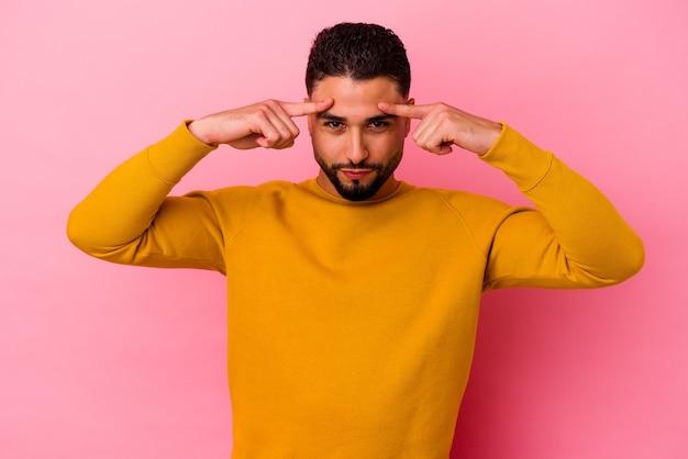 Jonge gemengd ras man geïsoleerd op roze achtergrond gericht op een taak, wijsvingers hoofd te houden.