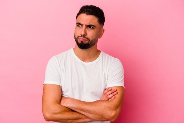 Jonge gemengd ras man geïsoleerd op roze achtergrond moe van een repetitieve taak.
