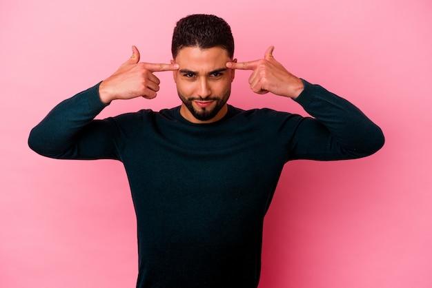 Jonge gemengd ras man geïsoleerd op roze gericht op een taak, wijsvingers hoofd wijzend.
