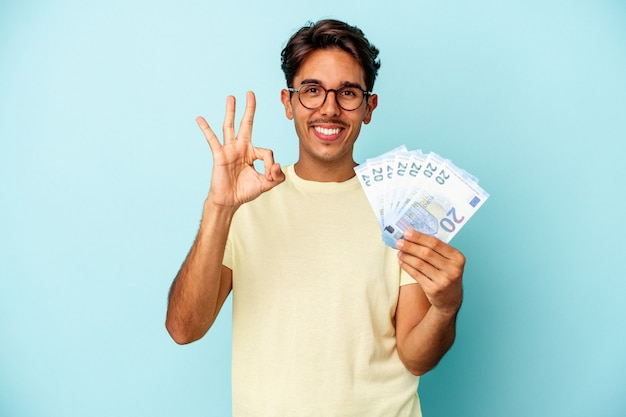 Jonge gemengd ras man met rekeningen geïsoleerd op blauwe achtergrond vrolijk en zelfverzekerd weergegeven: ok gebaar.